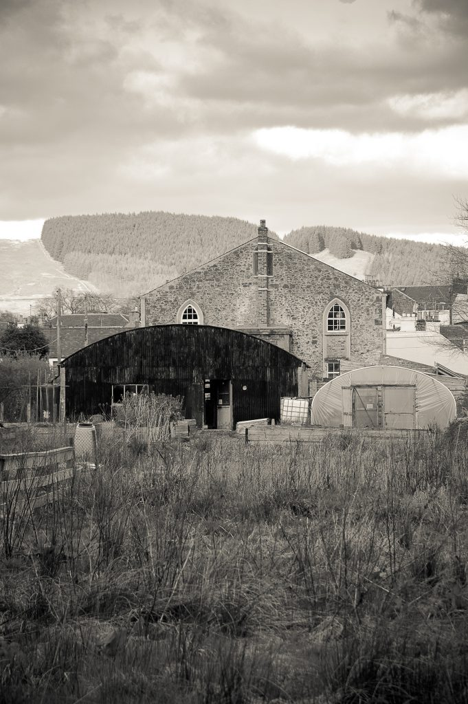 Side view of the main building with the shed and polytunnel in front.